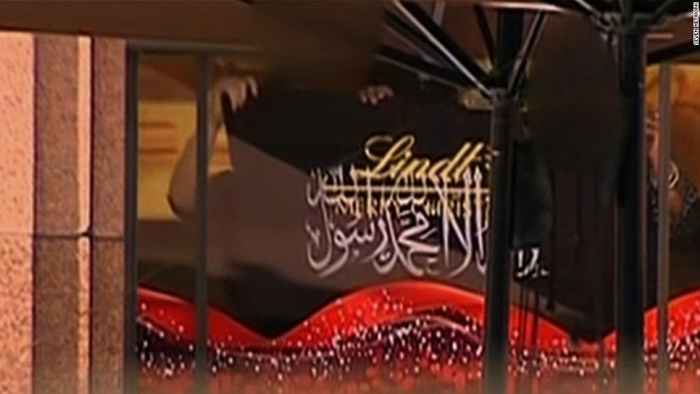Hostages behind the cafe's window hold up a black flag with Arabic script on December 15.