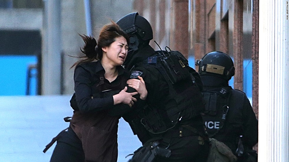 A hostage runs toward police on December 15. She was one of five people seen fleeing the cafe.