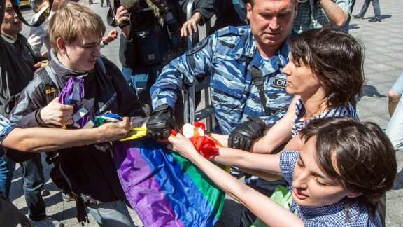 Caption:A man (L) takes away a rainbow flag as a policeman detain gay rights activists during their protest in central Moscow on May 31, 2014. Riot police on May 31 arrested two women as a small group of gay rights activists tried to stage a rally in central Moscow dedicated to Conchita Wurst, the bearded Austrian transvestite who won this year