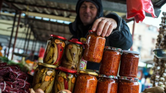 "Street markets are also a big part of life in Belgrade. Pictured here is a vendor selling jars of homemade ""Ajvar,"" a type of relish mainly made from roasted red bell peppers."