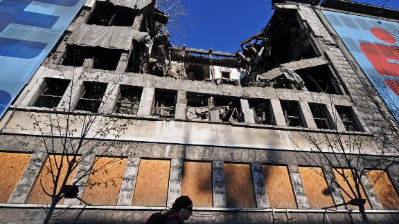 A woman walks on March 22, 2014 in front of the building of the former federal Interior Ministry in Belgrade, which was destroyed during the 1999 NATO air campaign against Serbia and Montenegro.