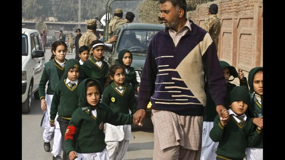 A plainclothes officer escorts rescued students away from the school.
