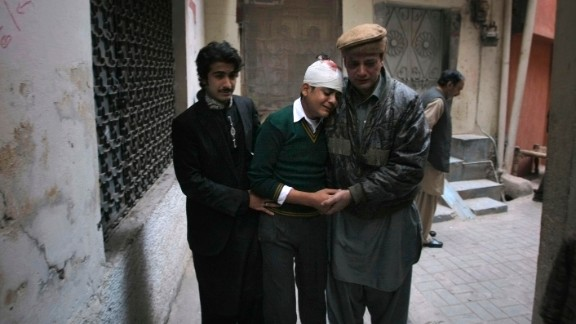The uncle and cousin of injured student Mohammad Baqair comfort him as he mourns the death of his mother, a teacher who was killed in the attack.