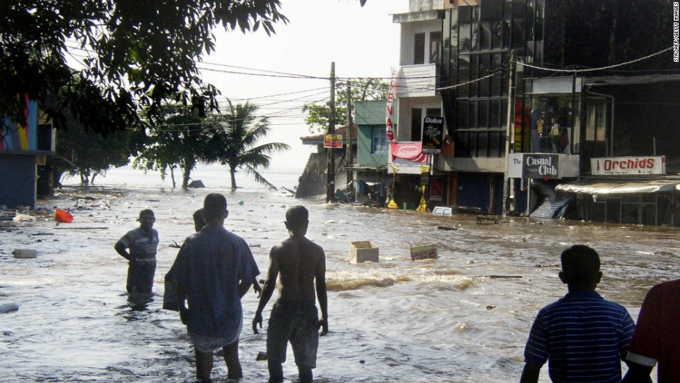Sri Lankan pedestrians walk through floodwaters in a main street in Galle, after the coastal town was hit by a tidal wave.