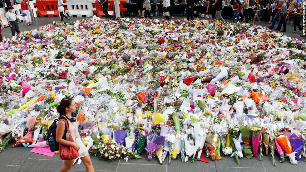 A woman walks past flowers placed by people as a mark of respect for the victims of Martin Place siege on Tuesday, December 16.