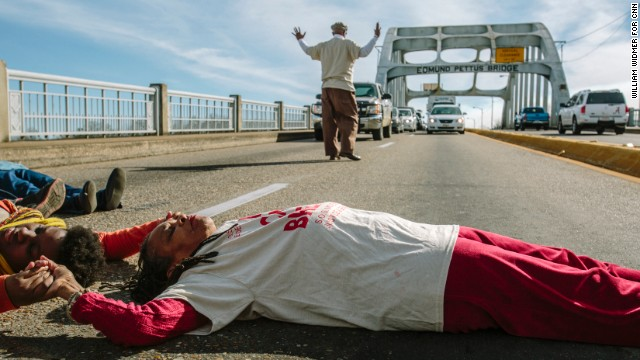 Faya Rose Toure (in white shirt) lies on the Edmund Pettus Bridge to block traffic in a protest against a police shooting in Selma.