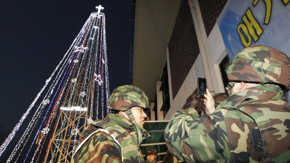 South Korean soldiers stand guard as Christians stage a lighting ceremony in front of a Christmas tree atop a military-controlled hill near the tense land border in Gimpo, west of Seoul, on December 21, 2010. North Korea has objected to Christmas trees at the border since the 1960s.