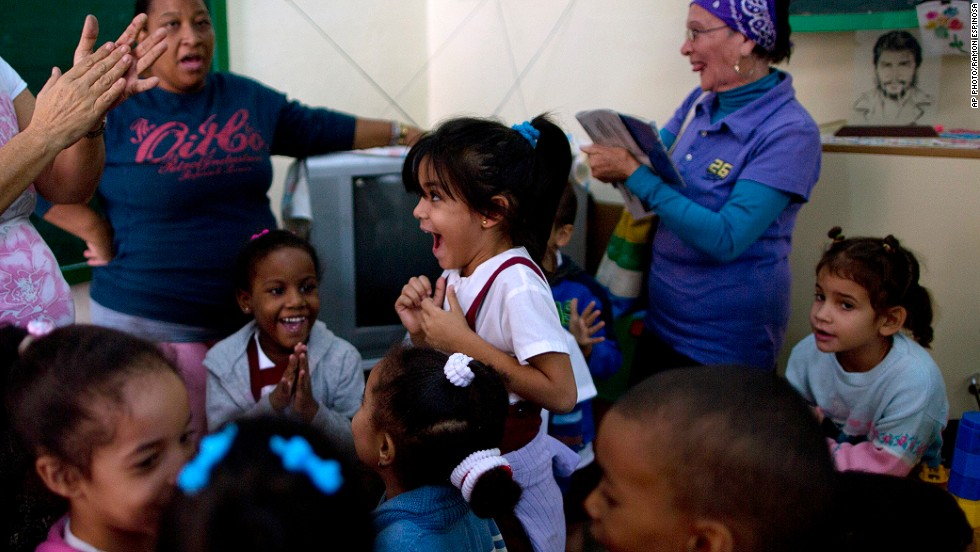 "DECEMBER 18 - HAVANA, CUBA: Students and teachers celebrate at a school after listening to a live, nationally broadcast speech by Cuba's President Raul Castro about the country's <a href=""http://cnn.com/2014/12/17/politics/cuba-alan-gross-deal/index.html"">restoration of relations with the United States.</a>"