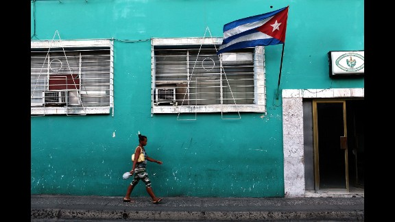 A woman walks under a Cuban flag in Santiago de Cuba in March 2012, just before a visit from Pope Benedict. The city is considered a cradle of Cuba's revolution.
