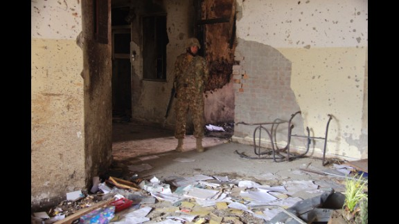 A soldier walks outside the Pakistani school that was attacked by members of the Pakistani Taliban on Tuesday, December 16. CNN cameraman Javed Iqbal took these photos in the aftermath of the attack, which killed more than 140 people.