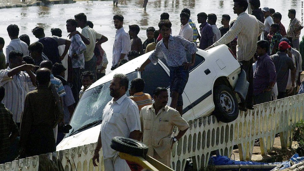 Bystanders watch rescue operations at Marina Beach in Chennai on December 26, 2004. Powerful waves sent this car crashing onto a road barrier.