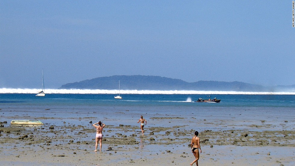 Foreign tourists react as the first of six tsunami start to roll towards Hat Rai Lay Beach, near Krabi in southern Thailand on December 26, 2004.