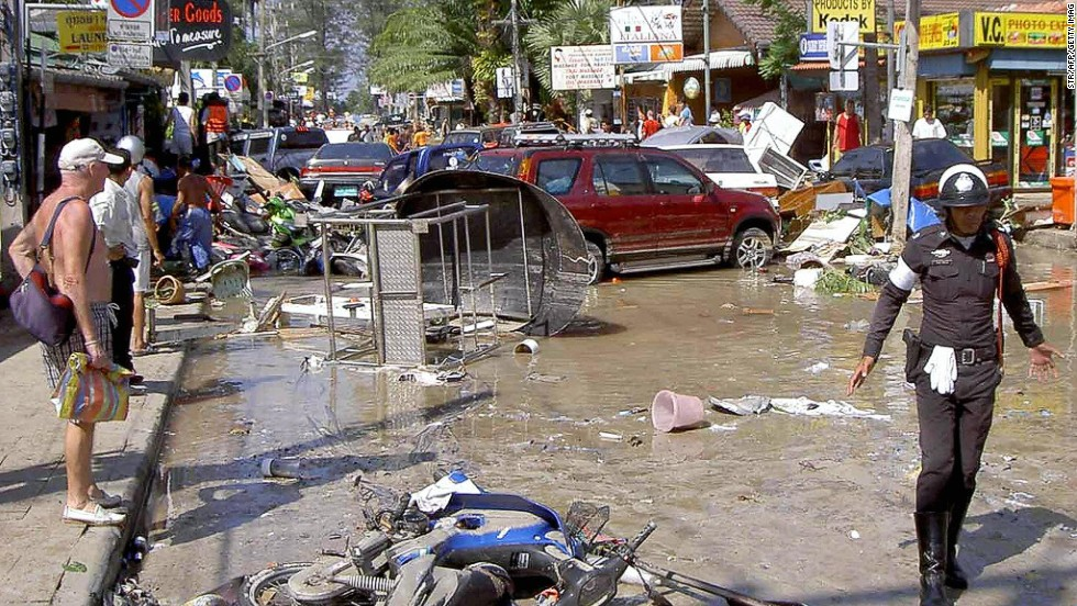 Foreign tourists look at damage caused by the tsunami in Phuket on December 26, 2004.