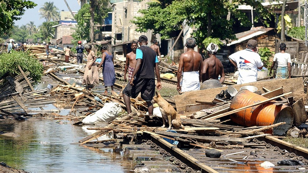Residents wade through the trail of destruction along the coastal railway line in the southern town of Lunawa after tsunami tidal waves lashed more than half of Sri Lanka's coastline.
