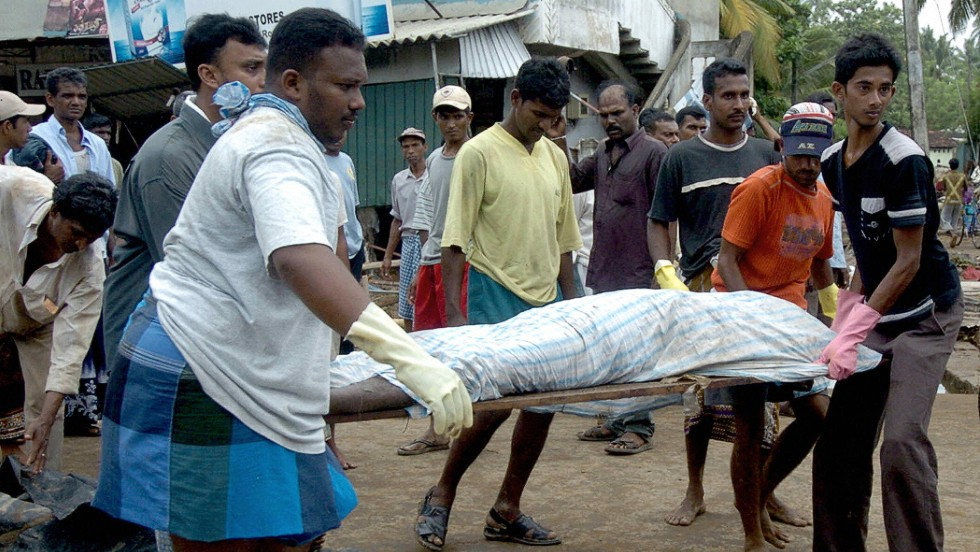Sri Lankan health officials and relatives carry the body of a dead man away in Galle on December 27, 2004.