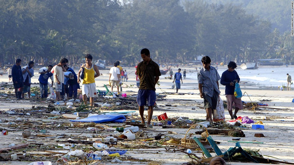 People walk through debris along the shoreline of Pathong beach of Phuket island, December 27, 2004, a day after the disaster.