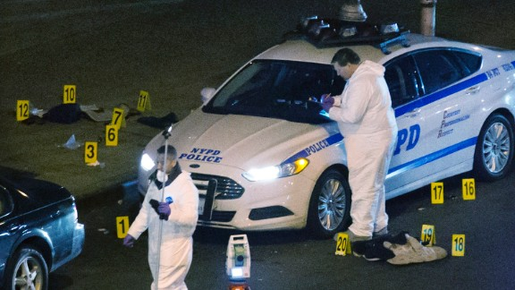 Investigators work the scene where two NYPD officers were shot December 20, in the Bedford-Stuyvesant neighborhood of Brooklyn, New York.
