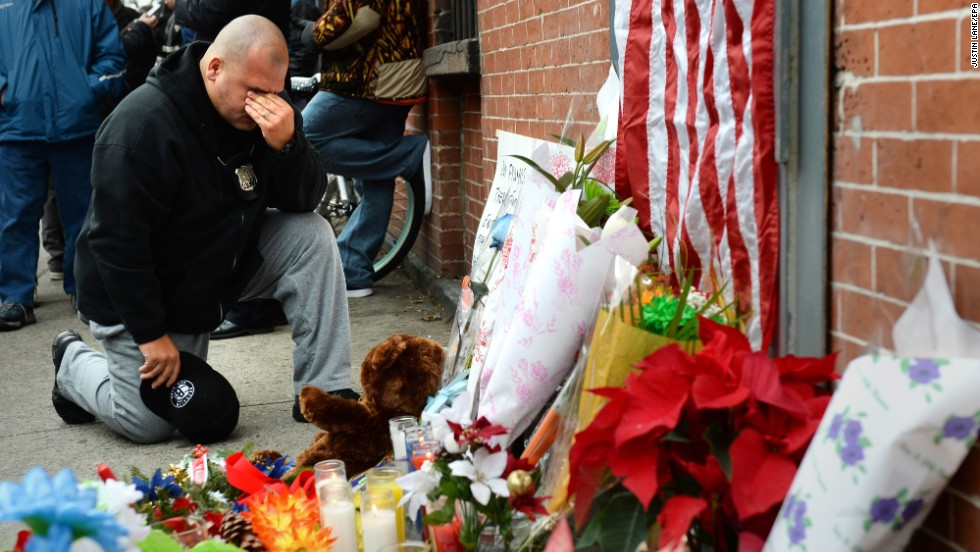 A New York City police officer kneels on Sunday, December 21, in front of a small memorial for two police officers who were killed  in Brooklyn, New York, on Saturday.