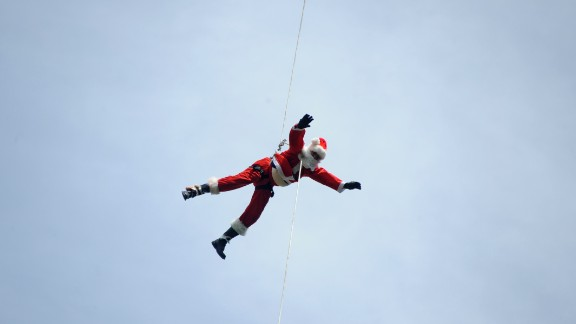 Firefighter Hector Chaco maneuvers down a cable from a bridge to deliver presents to children as Santa in Guatemala City.