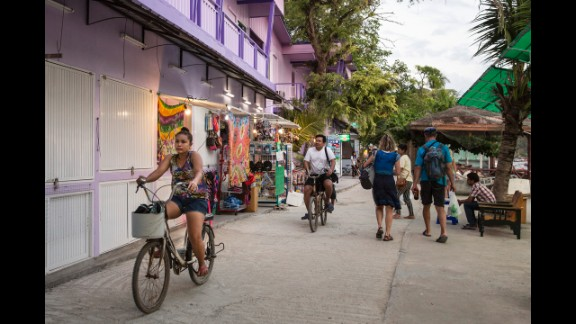 Ten years later, people ride bicycles and stroll along a path in Ton Sai Bay.