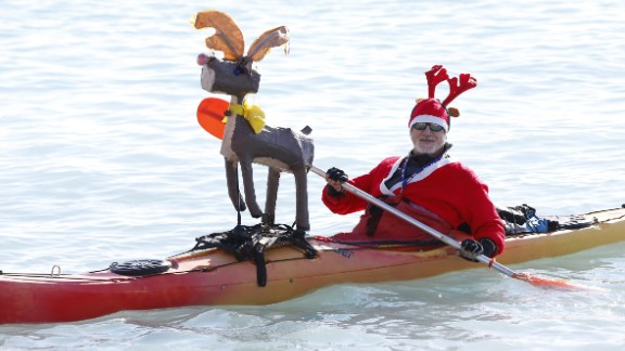 A man in a Santa outfit paddles a canoe decorated with a reindeer during the traditional Christmas bath in Nice, France.