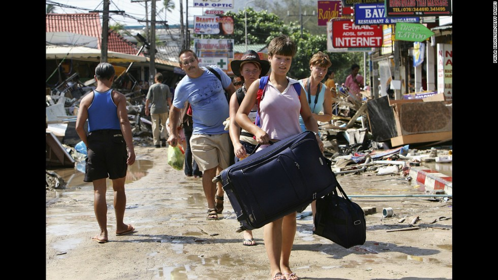 Travelers walk past devastation, carrying their luggage, as they head to the airport on December 27, 2004. Patong Beach was one of the worst hit provinces of Phuket, Thailand.
