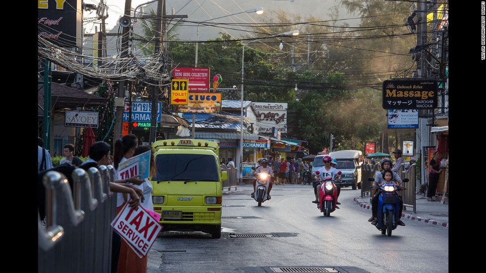 A view of Patong Beach 10 years later shows motorbikes, vans, cars and taxis traveling along a busy Patong road.