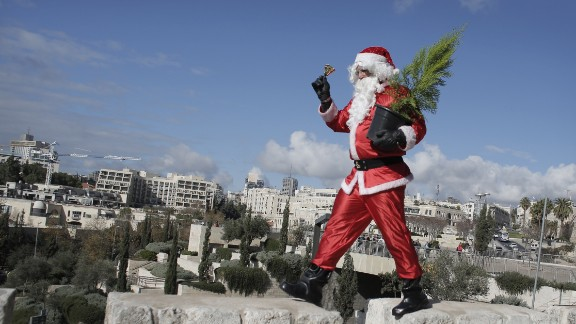 A Palestinian Santa distributes Christmas trees along the wall of Jerusalem's Old City.