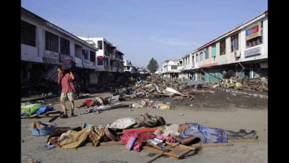 A man covers his mouth as he walks amid bodies and debris in Banda Aceh on December 28, 2004.