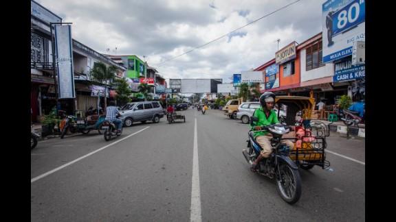 People drive along W.R. Supratman Street 10 years after the tsunami.