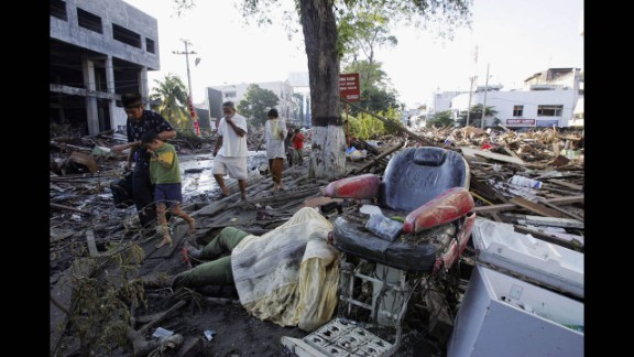 Locals in Banda Aceh walk with their faces covered as they pass bodies and debris on December 28, 2004.