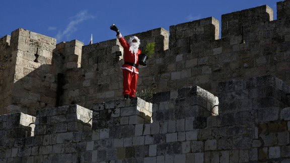 Santa waves to passers-by as he walks along Jerusalem's Old City walls.