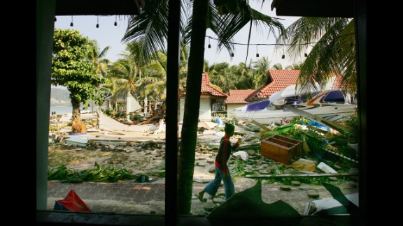 A Thai woman walks by the devastation at a hotel along Patong Beach on December 27, 2004, in Phuket.