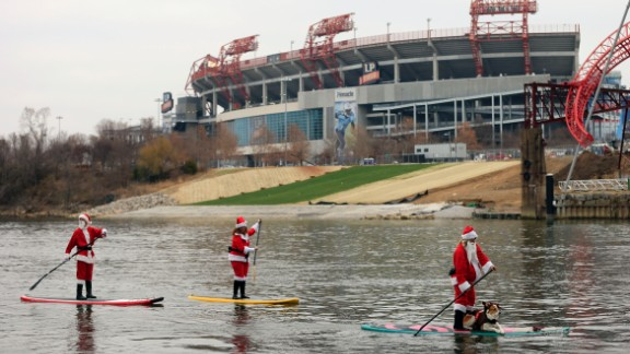 People donning Santa costumes paddle on the Cumberland River in Nashville, Tennessee.
