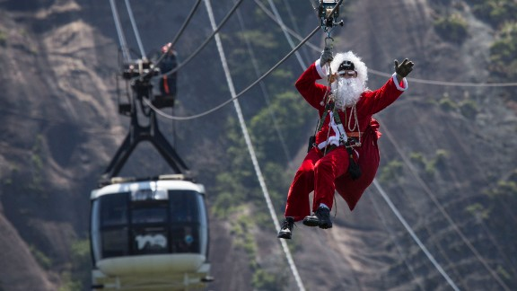 Santa takes a zip line away from Sugarloaf Mountain after riding on top of a cable car in Rio de Janeiro.