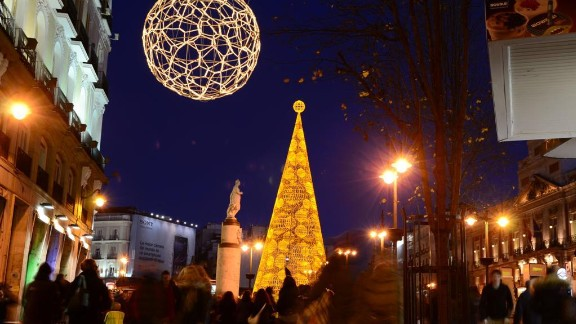 Bright Christmas decor adorns Puerto del Sol, a bustling square in Madrid, Spain.