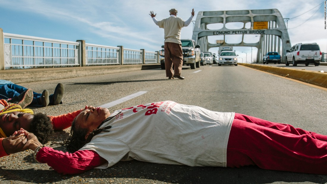 "Longtime activist Faya Rose Toure leads a ""die-in"" on the Edmund Pettus Bridge, a prominent landmark in Selma, Alabama. Police attacked civil rights marchers on the bridge 50 years ago at a protest that became known as ""Bloody Sunday."" Toure evokes Selma's past in her attempts to change the present."
