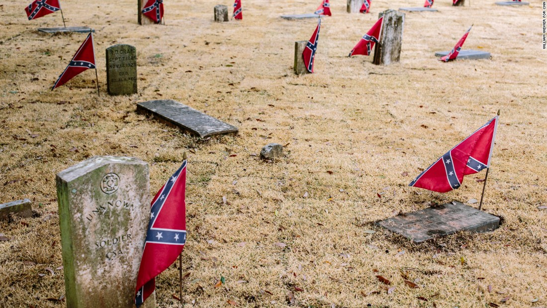 "Confederate flags mark graves at Live Oak Cemetery. Controversy erupted after the city approved a new monument at the cemetery that honors Nathan Bedford Forrest, a Confederate general accused of massacring black soldiers and a ""grand wizard"" of the Ku Klux Klan."