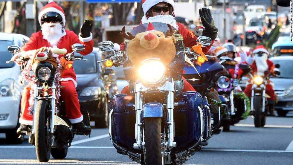 Motorcyclists in Santa and reindeer outfits ride through the streets of Tokyo.