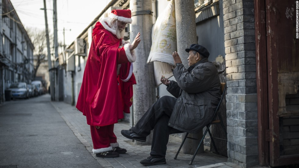 A Santa gives out sweets to a man in Beijing on December 23.