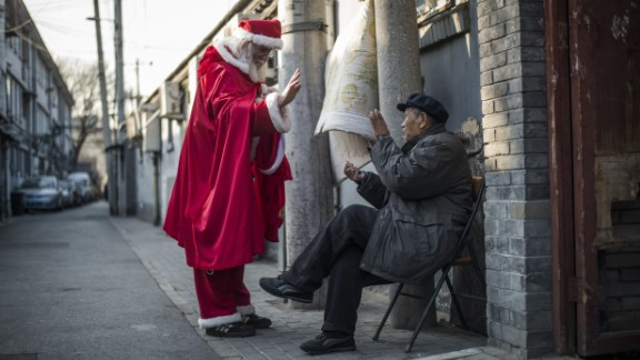 A Santa gives out sweets to a man in Beijing.