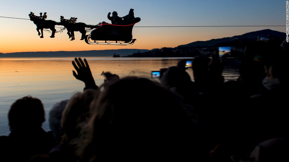 "With help from a cable, Santa and his reindeer ""fly"" over Lake Geneva as part of the Christmas Market in Montreux, Switzerland, on December 23."
