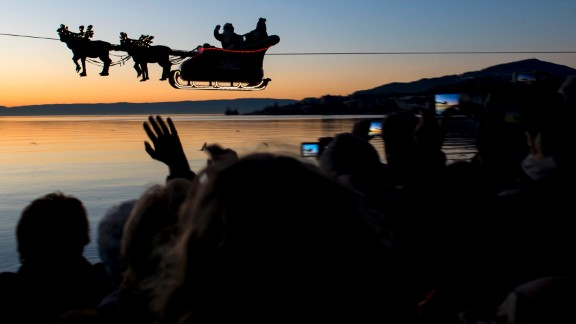 "With help from a cable, Santa and his reindeer ""fly"" over Lake Geneva as part of the Christmas Market in Montreux, Switzerland."