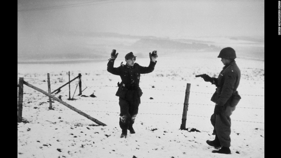 Mid-December 1944 saw the beginning of the six-week Battle of the Bulge on Europe's Western Front. War photographer Robert Capa immersed himself with Allied troops. Here, an American soldier points a gun at a German prisoner of war.