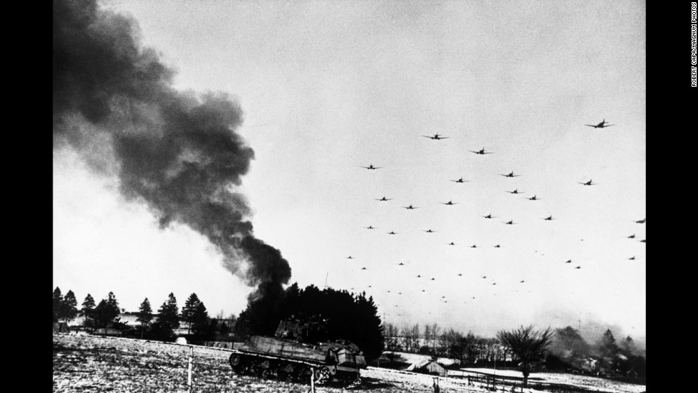 An American tank burns while transport planes fly overhead during the Battle of the Bulge.
