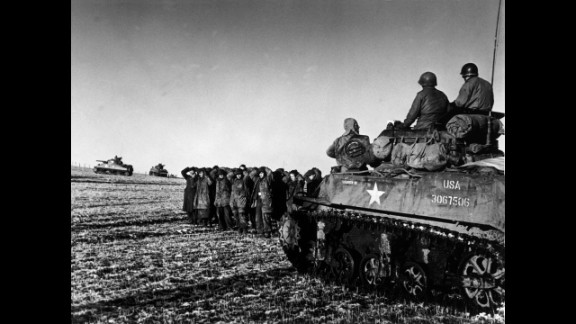 American troops ride on a tank while German POWs are held nearby.
