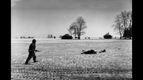 An American soldier walks past a casualty during the Battle of the Bulge.