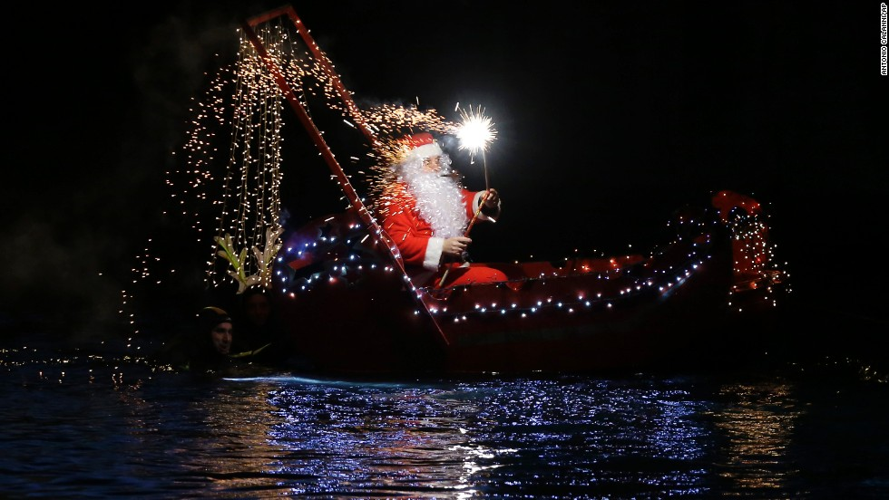 A Santa Claus lights a flare while riding in a boat Wednesday, December 24, in Imperia, Italy.