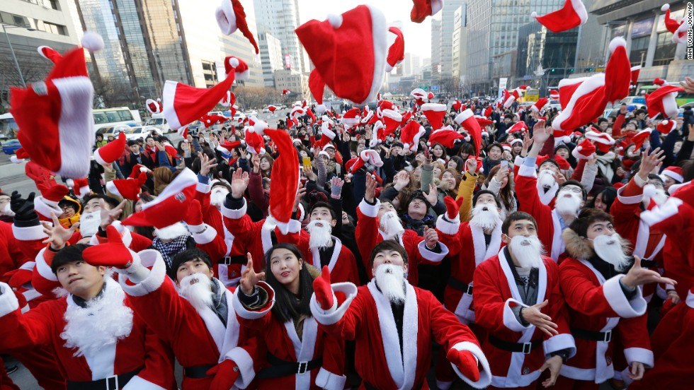 Volunteers in Santa outfits toss their hats into the air before delivering gifts to the poor in Seoul, South Korea.