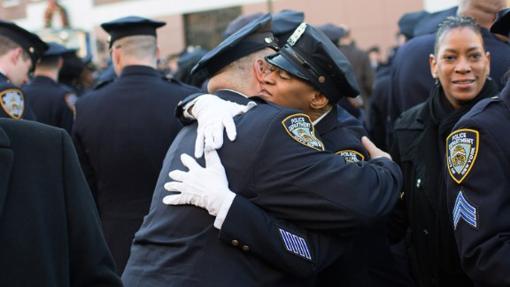 NYPD officers embrace before the funeral of the slain officer.